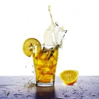yellow drink with splash, ice cubes and flying lemons slices, refreshing beverage from juice, soda or ice tea isolated on a blue table against a white background, selective focus