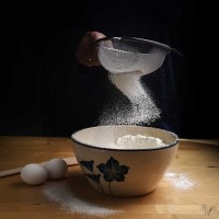 flour falling in a bow from a sieve into a bowl on a wooden kitchen worktop at baking preparation, dark background with copy space, selected focus
