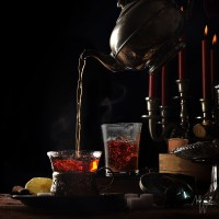 pouring hot steaming tea from a vintage teapot into  glass cups on a rustic table setting with candles and candies, cozy break in the dark winter time, black background with copy space, selective focus