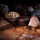 Chocolate pralines and cocoa powder on rustic wood as a love gif