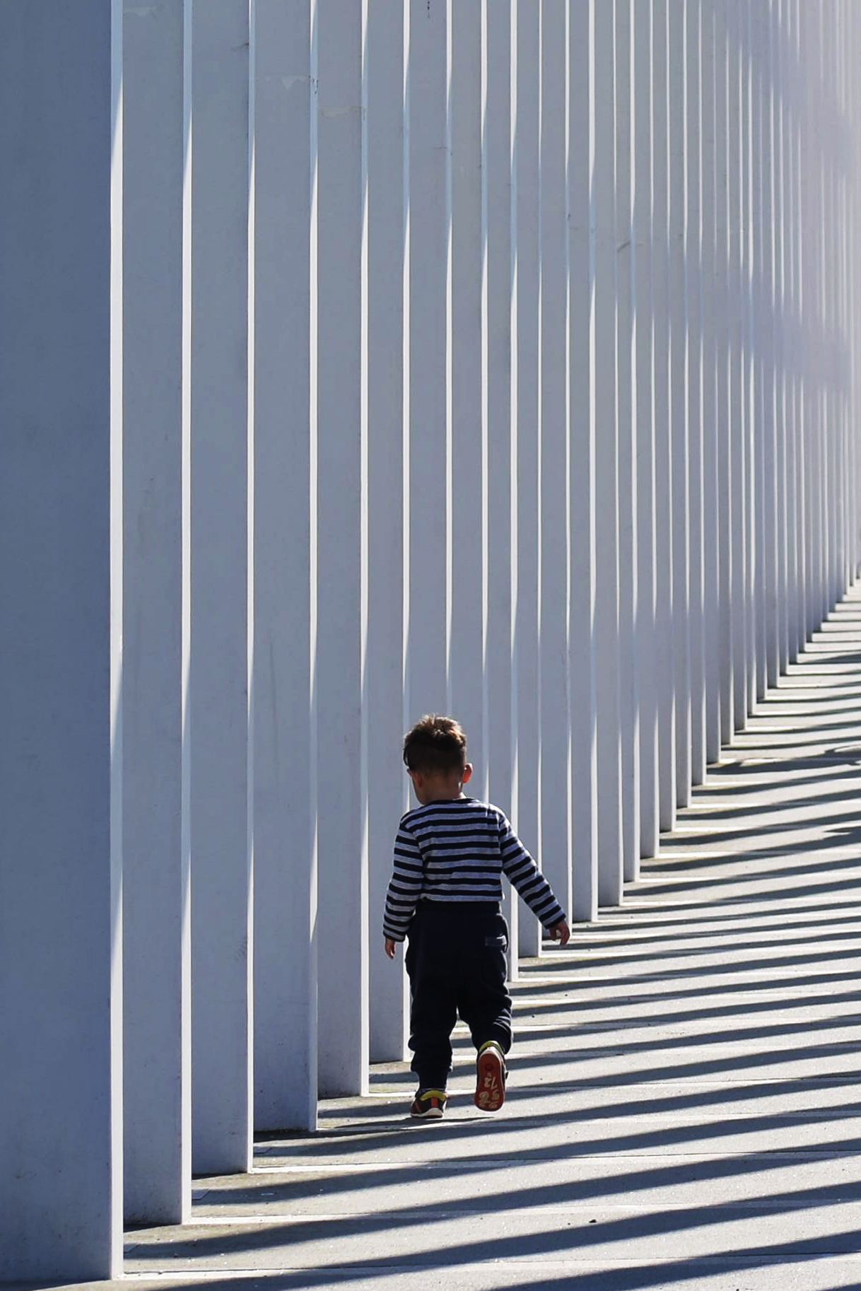 Striped concept, little boy with a striped pulli running through the light and shadow stripes of a rectangular portal made of white painted concrete, seen in Schwerin, northern Germany
